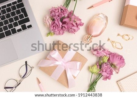 Scattered laptop, gifts, flowers and feminine accessories on a beige background. Online celebrate or shopping concept. Royalty-Free Stock Photo #1912443838