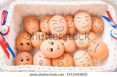 Eggs with different mood expressions by draw humor cartoon face on eggshells heap in weave basket, a symbol of Easter as a fun traditional holiday in April. Creative idea concept of group gathering.