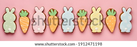Easter greeting card with colorful rabbits, eggs, chickens and carrots gingerbread cookies on pink background with copy space. Mock up. Banner. Top view.