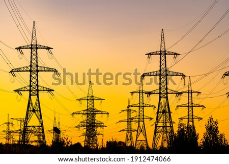 Evening light. Sunset casting red and orange light. Silhouettes of the electric power masts and cables, pylons. Electricity power station. Royalty-Free Stock Photo #1912474066