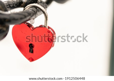 Love for sweethearts and relation memory in form of a lock as symbol for love, romance, eternity and endless love for couples on Valentines Day at a chain fence to celebrate wedding or romantic day