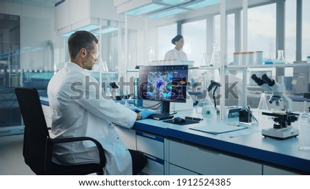 Advanced Medical Science Laboratory: Medical Scientist Working on Personal Computer with Screen Showing Virus Analysis Software User Interface. Scientists Developing Vaccine, Drugs and Antibiotics. Royalty-Free Stock Photo #1912524385