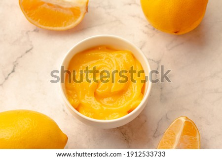 Delicious homemade tangy lemon curd decorated with fresh fruit on marble background.Top view. Royalty-Free Stock Photo #1912533733