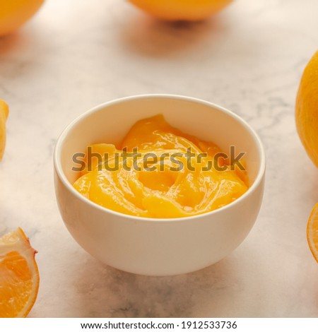 Homemade fresh pudding or tangy lemon curd in a white bowl.Selective focus. Royalty-Free Stock Photo #1912533736