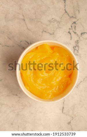 Homemade fresh pudding or tangy lemon curd in a white bowl on marble background.Top view. Royalty-Free Stock Photo #1912533739