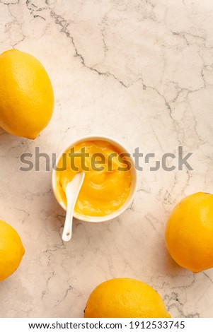 Homemade tangy lemon curd decorated with fresh fruit on marble background.Top view. Copy space for text. Royalty-Free Stock Photo #1912533745