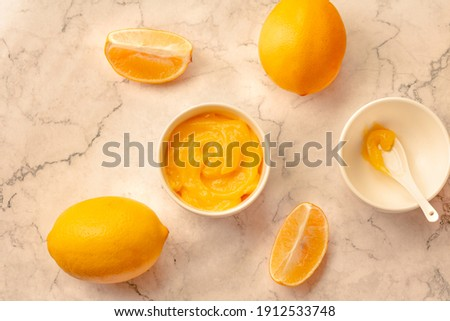 Homemade tangy lemon curd decorated with fresh fruit on marble background.Top view. Copy space for text. Royalty-Free Stock Photo #1912533748