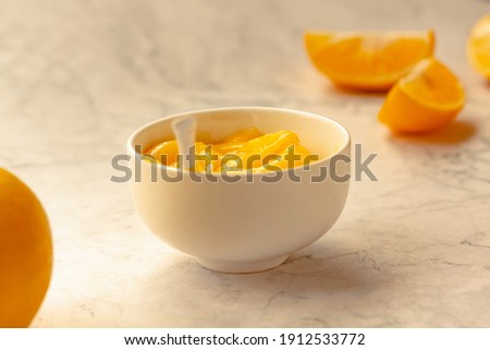 Composition with delicious Yellow lemons and Lemon curd in a sausepan white bowl on marble background. Royalty-Free Stock Photo #1912533772