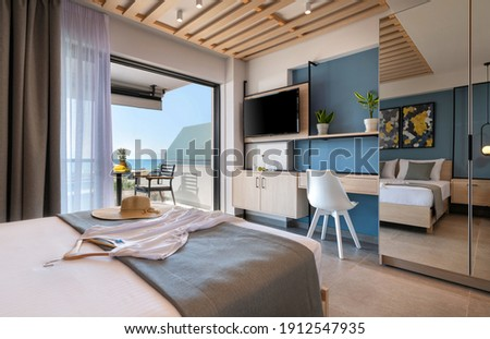 Modern loft style bedroom with metal details, wooden furniture, mirror wardrobe, abstract decor. Hotel apartment with sea view balcony, open air French window terrace