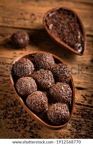Chocolate Easter egg stuffed with brigadeiros. Royalty-Free Stock Photo #1912568770