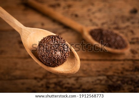 Chocolate brigadeiro in wooden spoon. Brigadeiro, traditional Brazilian sweet. Royalty-Free Stock Photo #1912568773