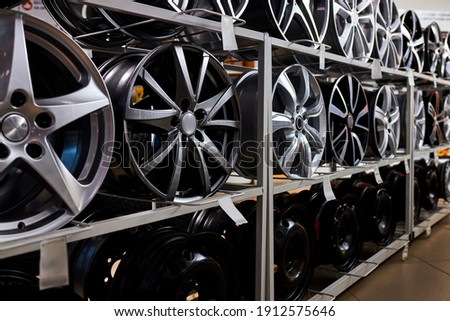 modern store with alloy wheels and tires, indoors in shop. a lot of discs for automobile, big assortment Royalty-Free Stock Photo #1912575646