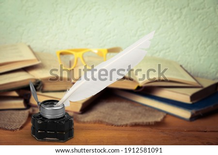 Old feather quill ink pen with inkwell and old books on wooden desk Royalty-Free Stock Photo #1912581091