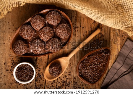 Chocolate Easter egg stuffed with brigadiers on wooden background. Royalty-Free Stock Photo #1912591270