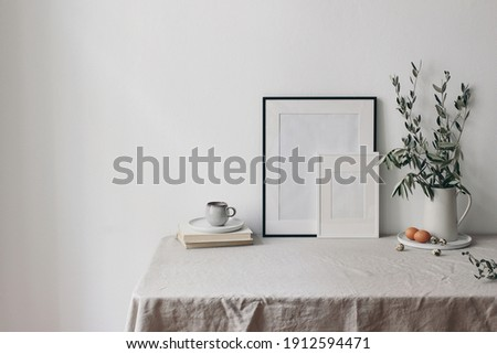 Spring, Easter breakfast still life. Cup of coffee, books and empty picture frames mockups. Linen tablecloth. Olive tree branches in ceramic jug. Hen, quail eggs. Farmhouse, Scandinavian interior.