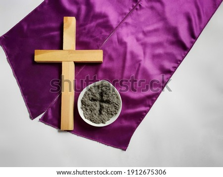 Lent Season,Holy Week and Good Friday concepts - photo of wooden cross and bowl of ash in vintage background. Stock photo.