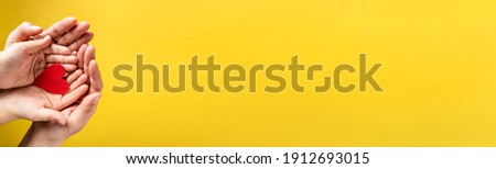 Red hart on palms of mother and son - Caucasian woman and child holding red hart shape above the modern abstract yellow background with copy space - Love care protection motherhood and family concept Royalty-Free Stock Photo #1912693015