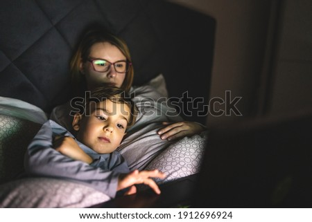 Mother and son watching movie or cartoon using laptop in bed at nighttime - Small boy and his mom using computer while lying in bed at night in dark room - leisure activity family bedtime concept Royalty-Free Stock Photo #1912696924
