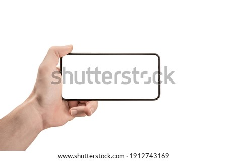 mockup phone horizontal. Hand Holding The Black Smartphone and Modern Frameless Design. Isolated man left hand holding black horizontal cellphone phone. watch tv streaming video movies online Royalty-Free Stock Photo #1912743169