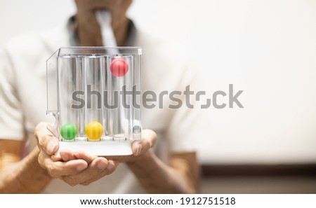 The old patient hand holding the Tri-ball incentive spirometry is medical equipment for post operation. The equipment for Lungs function testing and Pulmonary test. Royalty-Free Stock Photo #1912751518