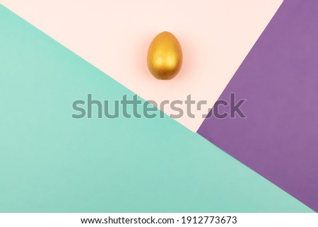 Abstract geometric paper background of pastel pink and purple colors with golden easter egg. Copy space for design.