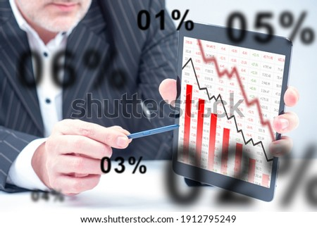 A man shows a falling graph on a tablet. Falling stock prices. The decline in revenue. The fall of stock indices. The crisis in the stock market. Problems of the securities market. Stock analytics.