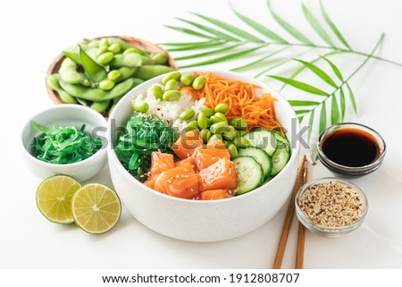 Poké bowl with fresh salmon, rice, chukka salad, edamame beans, carrots and cucumber. Bowl of healthy food on white background  Royalty-Free Stock Photo #1912808707