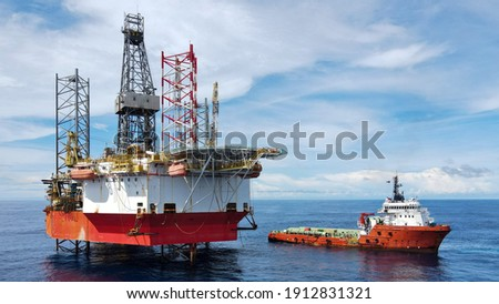 A jack up rig with an anchor handling vessel during cargo operation at sea. Royalty-Free Stock Photo #1912831321