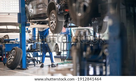 Mechanic inspecting car suspension detail and wheel car of lifted automobile at repair service station. Car service station. Preventive maintenance. Royalty-Free Stock Photo #1912841464