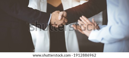 Unknown businesspeople are shaking their hands after signing a contract, while standing together in a sunny modern office, close-up. Business communication, handshake, and marketing concept Royalty-Free Stock Photo #1912886962