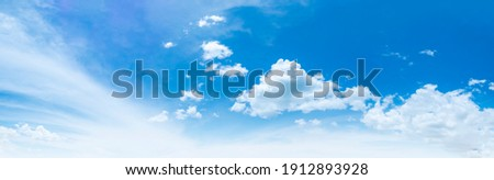 Blue sky and white clouds floated in the sky on a clear day with warm sunshine combined with cool breeze blowing against the body resulting in a miraculous refreshing like paradise. Royalty-Free Stock Photo #1912893928