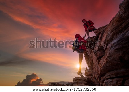 Young asian couple climbing up on the mountain,hiking and team work concept. Royalty-Free Stock Photo #1912932568