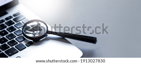 Magnifying glass put on close up of Laptop computer. Internet search concept. Wide banner or panorama.