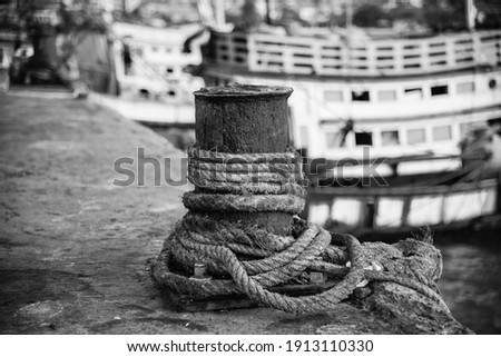 A steel pole for tying a fishing boat at the port of Si Racha District, Thailand. Photographed in black and white.