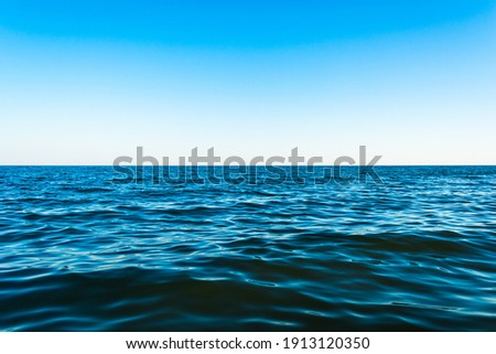 Small sea waves against the blue sky and white horizon Royalty-Free Stock Photo #1913120350