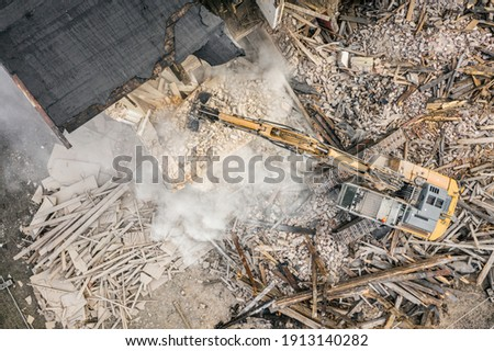 Yellow excavator destroys building. Heavy duty machine is demolishing a brick building. Demolition of the building . Demolition construction work aerial drone photo  Royalty-Free Stock Photo #1913140282