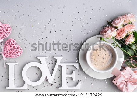 Cup of coffee, box with a gift and pink roses on a festive gray background. flat lay. Copy space. View from above.