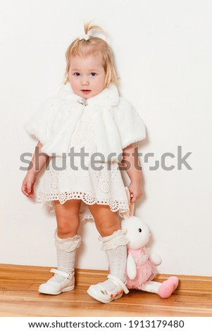 Baby Girl in a white dress and golf courses against a white background