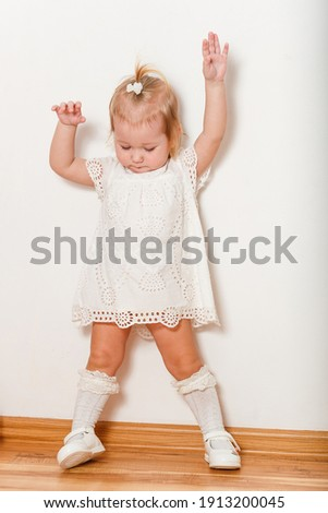 Cute half-old blonde girl in a white dress and full-length golf cart poses