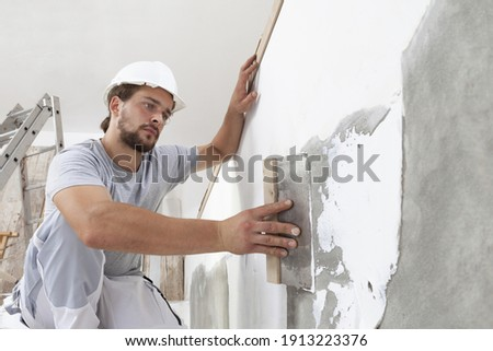 Hands man plasterer construction worker at work with trowel, plastering a wall, closeup Royalty-Free Stock Photo #1913223376
