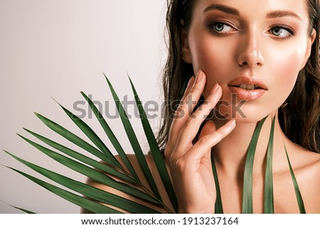 White woman with healthy skin of body and palm leaves. Tanned body of an attractive girl with green plants. Large palm leaves cover the body. Royalty-Free Stock Photo #1913237164