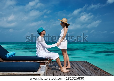 Couple on a tropical beach jetty at Maldives #191325830