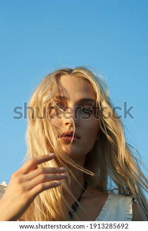 Gorgeous young woman in white romantic clothes on blue sky background. Sunny day. Blonde model with big beautiful eyes and nice lips. Calm and balance. Fashionable look. Beauty portrait. Headshot   Royalty-Free Stock Photo #1913285692