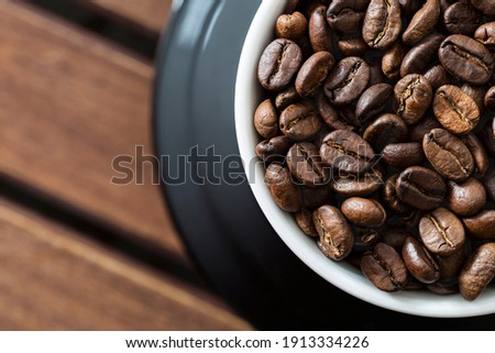 A high resolution stock photo of roasted coffee beans in a white cup on table, directly above , macro shot