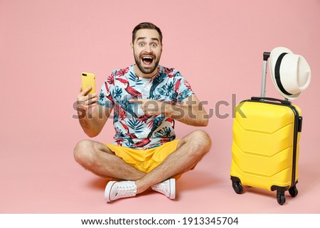 Full length excited traveler tourist man sit on floor point index finger on mobile cell phone booking hotel taxi isolated on pink background. Passenger travel on weekend. Air flight journey concept Royalty-Free Stock Photo #1913345704