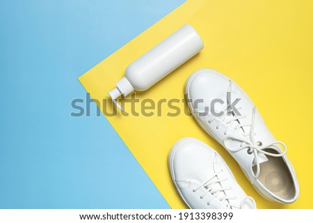 White leather sneakers, plastic bottles of cleaning products for shoes on blue yellow background flat lay top view. Natural leather shoe care, spray, foam, shoe deodorant, cosmetic shoe products Royalty-Free Stock Photo #1913398399