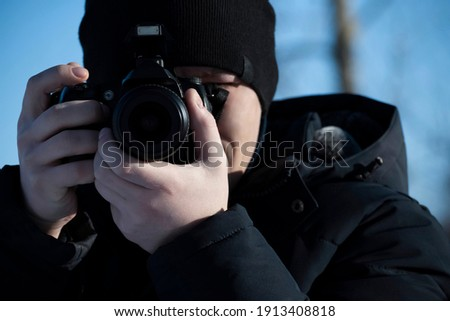 Photographer man in warm clothes in the winter holds the camera up close to my face taking pictures of nature. An article about winter photography, the use of photographic equipment in the cold season