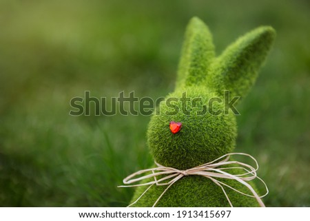 Close up Easter bunny rabbit statuette and basket with easter eggs on the green grass lawn background. Easter egg hunt in the garden. Selective focus, copy space Royalty-Free Stock Photo #1913415697