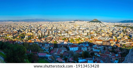 Panoramic aerial view of city of Athens, Attica, Greece. View from Acropolis of Athens. Skyline with mass of houses, buildings, rooftops in the city center of Greek capital. Lycabettus Hill on right Royalty-Free Stock Photo #1913453428