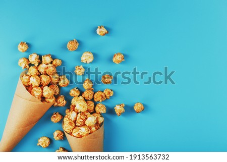 Caramel popcorn in a paper envelope on a blue background. Delicious praise for watching movie movies, serial, cartoon. Free space, close-up. Minimalistic concept.